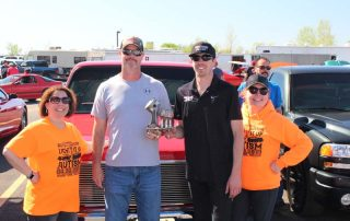 four people holding trophy in front of red truck
