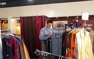 young man browsing a clothing rack