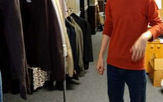 young man standing next to a clothing rack