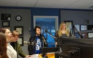 group of young people in a radio studio