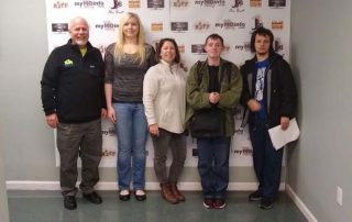 group of people in front of a wall display