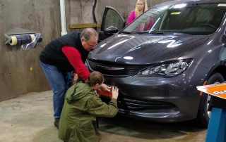 man showing young man how to work on a van