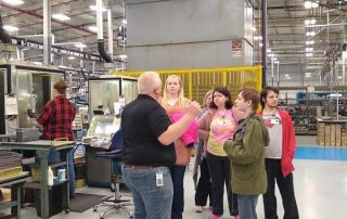 group of people being led on a factory tour
