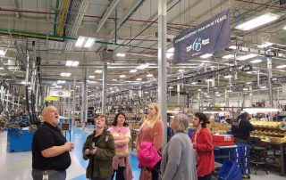 group of people touring a factory