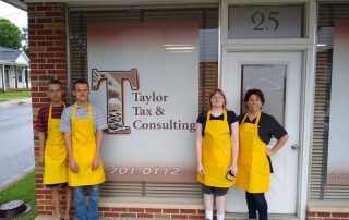 four people in yellow aprons outside tax business