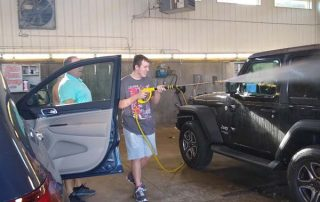 teen power washing a car from a different angle