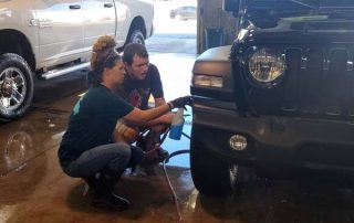 woman showing young man how to clean a car