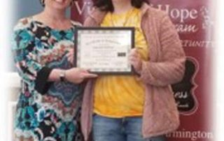 woman receiving certificate of completion from training program