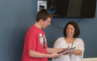 young man receiving certificate of graduation from Visions of Hope