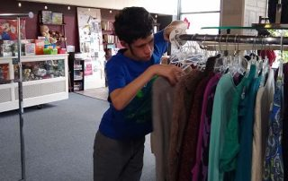 young man sorting clothes on a rack